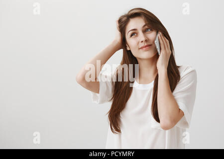 She cannot answer on tough question. Portrait of attractive female friend scratching head and looking up while smiling awkwardly and talking on smartp - Stock Photo