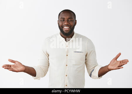 Indoor shot of charming carefree and happy cute dark-skinned bearded man in white shirt spreading palms aside and smiling broadly, inviting friend to  - Stock Photo