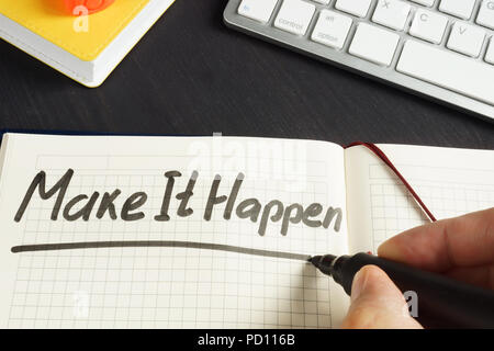 Man is writing Make It Happen in the note. - Stock Photo