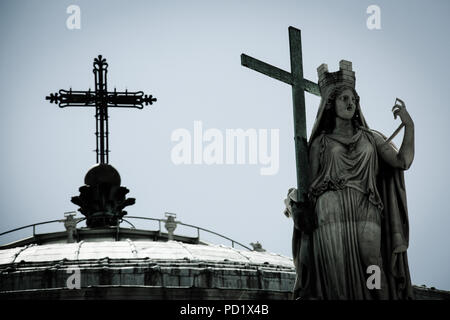 Saint statue holding a cross, as well as the cross on top of the cupola of the basilica San Francesco di Paola in Napoli, Italy - Stock Photo