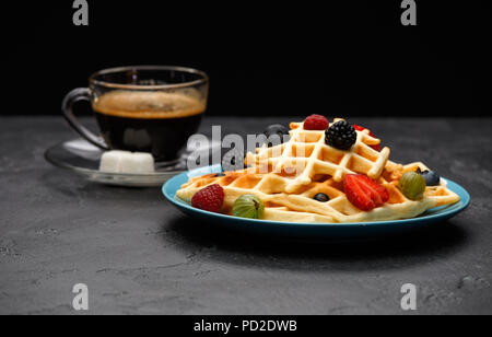 Photo of cup of black coffee with sugar with Viennese waffles with strawberries, raspberries - Stock Photo