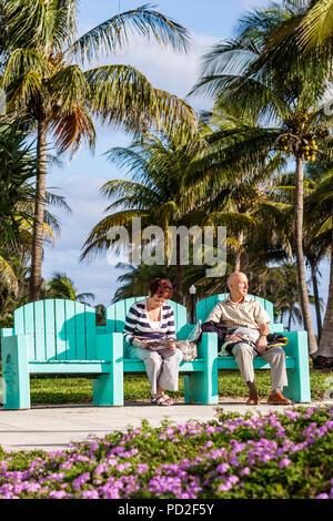 Miami Beach Florida Lummus Park coconut palm tree outdoors bench green man woman couple senior sitting relax reading read flower - Stock Photo