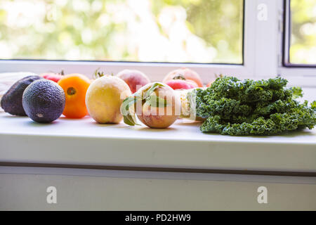 Seasonal summer fruits and vegetables on the windowsill. Healthy clean eating concept. - Stock Photo