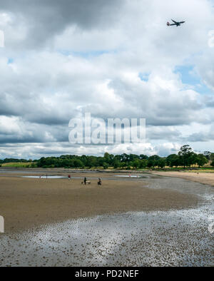 Dog walkers on wet sand at low tide with BA plane overhead, Cramond, Edinburgh, Scotland, UK with British Airways plane flying in sky overhead - Stock Photo