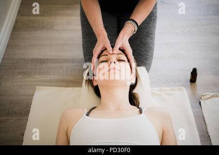 Woman enjoying head massage in yoga retreat - Stock Photo