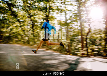 man runner fast running in autumn forest road blurred motion - Stock Photo