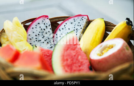 Sliced mix of tropical fruits in a wicker basket - Stock Photo