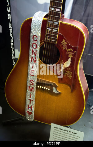 An acoustic guitar with a rhinestone strap belonging to singer Connie Smith at the Country Music Hall of Fame, Nashville, Tennessee, USA - Stock Photo
