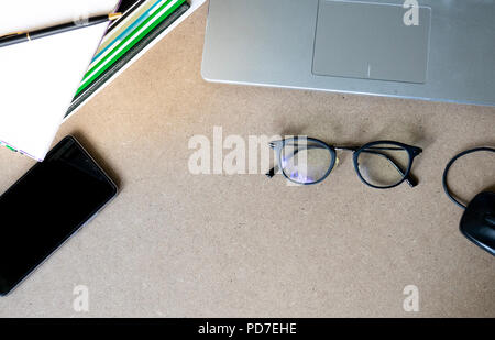 top view flat lay laptop, books, glasses, mouse and mobile phone on cork table background with copy space - Stock Photo