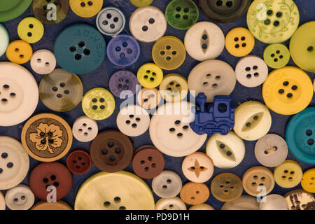 a selection or collection of colourful buttons one in the shape of a train. - Stock Photo