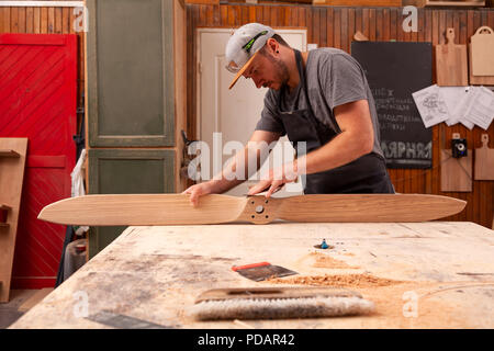 Experienced carpenter in work clothes and small buiness owner working in woodwork workshop,  using sandpaper for polishing wooden at worktable in work - Stock Photo