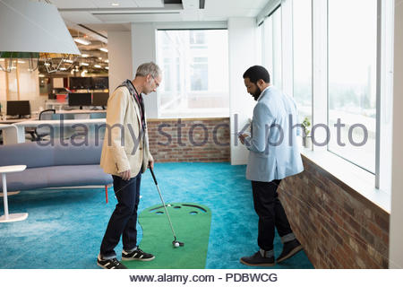 Creative businessman practicing putting in office - Stock Photo