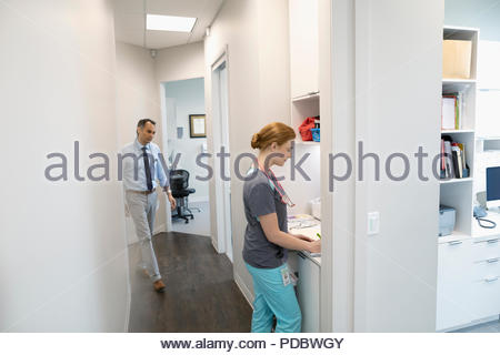 Female nurse and male doctor in clinic corridor - Stock Photo