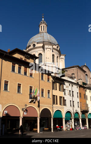 Pastel coloured buildings on the Piazza delle Erbe public square in Mantua, Italy. The cupola of the Basilica di Sant'Andrea chuch can be seen above t - Stock Photo