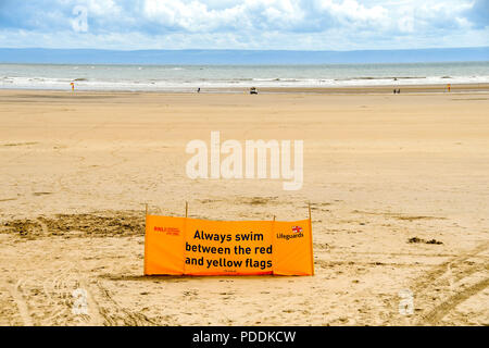 Large yellow RNLI water safety banner advising people to swim between the red and yellow flags - Stock Photo