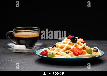 Photo of cup of coffee with sugar with Viennese waffles with strawberries, raspberries - Stock Photo