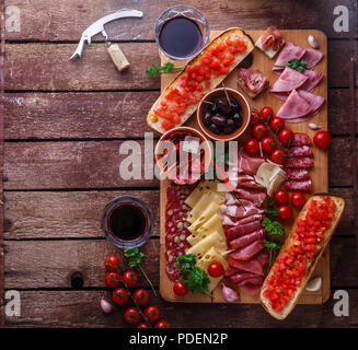 Meat and cheese appetizer set for red wine on rustic background, flatlay, copy space. - Stock Photo