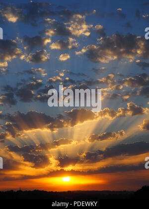 Portrait view of a spectacular sunset on a fine evening showing shades of orange with crepuscular rays of light through the altocumulus clouds. UK - Stock Photo
