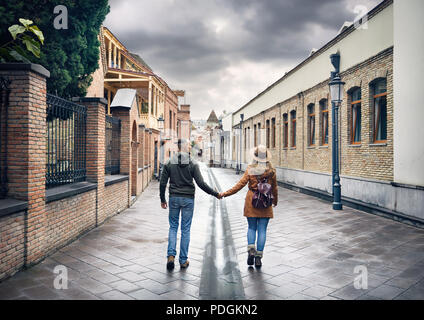 Tourist woman in brown hat and man in red shirt walking down old the Old streets of central Tbilisi, Georgia - Stock Photo
