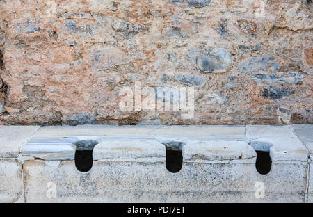 Stone communal toilets at Ephesus, an ancient Greek city settlement archaeological site on the Ionian coast near Selçuk, Izmir Province, Turkey - Stock Photo