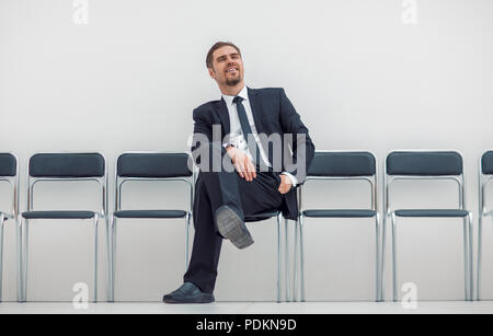 thoughtful businessman sitting in the office hallway - Stock Photo