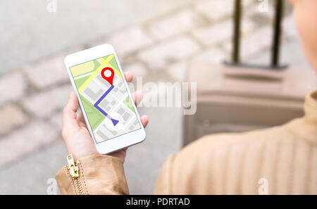 Woman navigating with mobile phone map application. Tourist with walking route on smartphone screen. Traveler with baggage using GPS. - Stock Photo