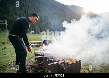 Family in Kyrgyzstan cooking dinner outside on campfire - Stock Photo