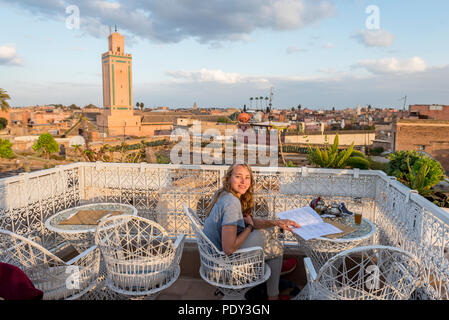 Young woman on a roof terrace reads the menu in the restaurant, view of the old town, mosque with minaret, evening mood - Stock Photo