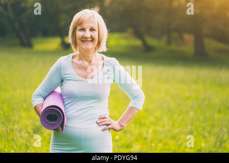 Portrait of sporty senior woman holding mat in the nature.Image is intentionally toned. - Stock Photo