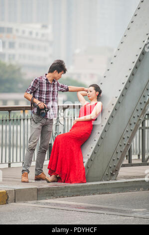 Shanghai, China - October 20, 2014. Photographer and a female fashion model during a photo shoot on a bridge over the Huangpu River in Shanghai. - Stock Photo