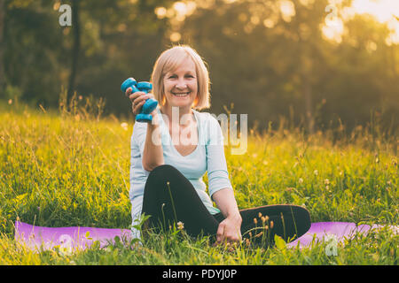Portrait of sporty senior woman holding weights outdoor.Image is intentionally toned. - Stock Photo
