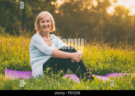 Portrait of sporty senior woman sitting on mat in the nature.Image is intentionally toned. - Stock Photo