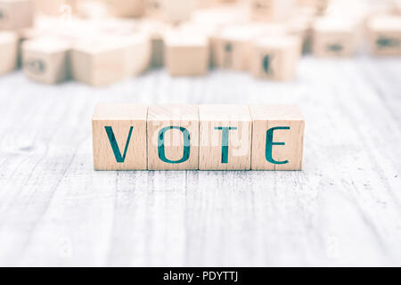 The Word Vote Formed By Wooden Blocks On A White Table, Reminder Concept - Stock Photo