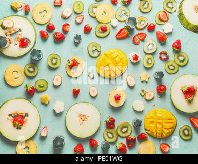 Various sliced fruits and berries on light blue background, top view, flat lay. Summer healthy food concept. Fruits salad ingredients selection - Stock Photo