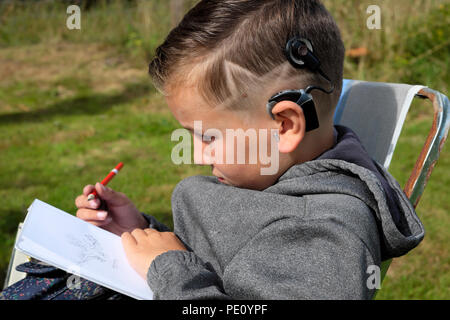 Side profile view of boy child 8 with star haircut sitting in the garden drawing in a sketch book wearing cochlear implant in the UK    KATHY DEWITT - Stock Photo