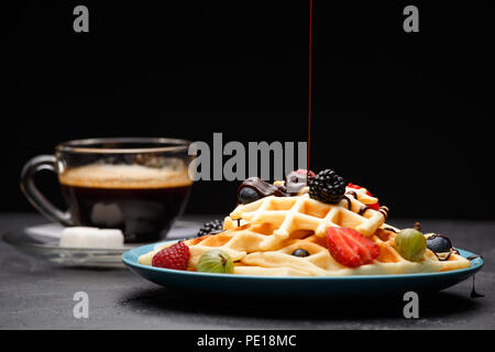 Photo of cup of black coffee with sugar with Viennese waffles with strawberries, raspberries, gooseberries and chocolate - Stock Photo