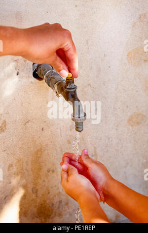 Woman hand open water tap and child washing his hands. Close up. - Stock Photo