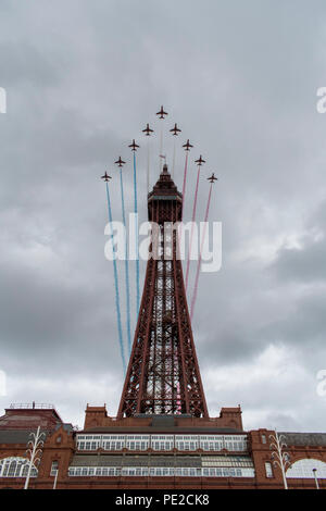 Blackpool, UK. 12 August 2018 - RAF Red Arrows fly over Blackpool Tower at the end of the annual Blackpool airshow. The Red Arrows flew to the backdrop of an emerging storm, and performed for a crowd of tens of thousand along Blackpool's promenade. Credit: Benjamin Wareing/Alamy Live News - Stock Photo