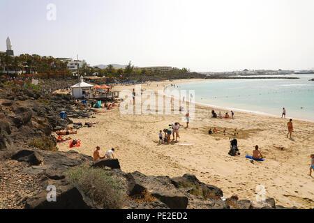 LANZAROTE, SPAIN - APRIL 18, 2018: Beautiful view of Playa Dorada beach with bathers on the sand, Lanzarote, Canary Islands - Stock Photo