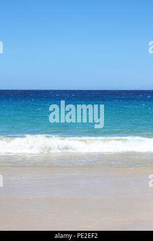 Multi hued blues in the Pacific Ocean with small waves rolling onto the white sand at Hapuna Beach, Waimea, Hawaii, USA - Stock Photo