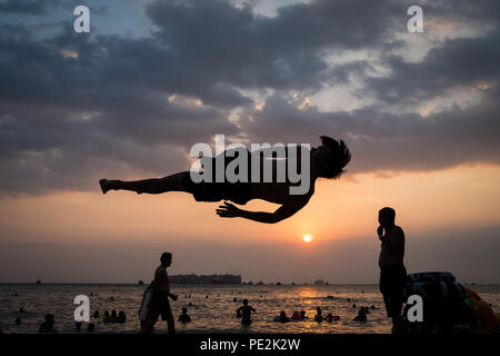 A young man practicing flips, almost appearing to be flying, at sunset on Front Beach, Vung Tau, Vietnam - Stock Photo