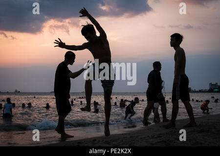 A young man preparing to jump at sunset on Front Beach, Vung Tau, Vietnam. - Stock Photo