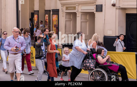 Hustle and bustle of people walking past theatre, young boy behind theatre barrier giving peace sign. London, England, UK - Stock Photo