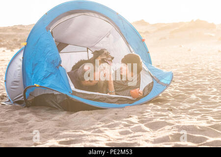 couple in outdoor free camping leisure activity have fun inside tiny home at the beach. Dog border collie behind them with love and friendship forever - Stock Photo