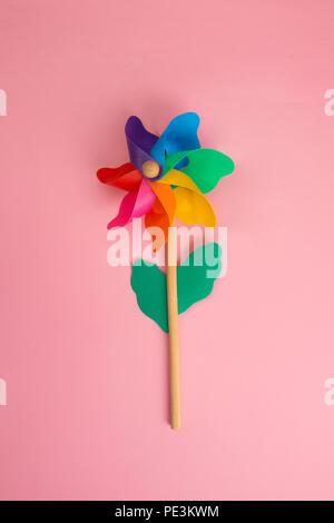 Colorful Pinwheel on pink paper - Stock Photo
