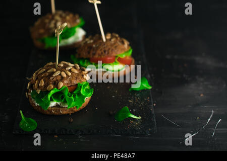 Green sandwich with salad, tomatoes, cucumbers and cream cheese on concrete desk. - Stock Photo