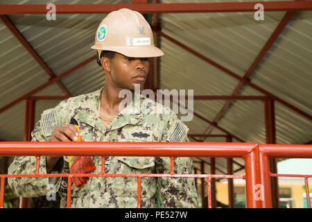 U.S. Navy Seabee Petty Officer 2nd Class Montrael Jackson, steel worker, 9th Engineer Support Battalion, 3d Marine Logistics Group, paints a gate for a new pathway built as part of the humanitarian civic assistance project at Binduyan Elementary School in Palawan, Philippines, during Amphibious Landing Exercise 2015 (PHIBLEX 15), Oct. 6. PHIBLEX 15 is an annual bilateral training exercise conducted with the Armed Forces of the Philippines in order to strengthen our interoperability and working relationships across a wide range of military operations from disaster relief to complex expeditionar - Stock Photo