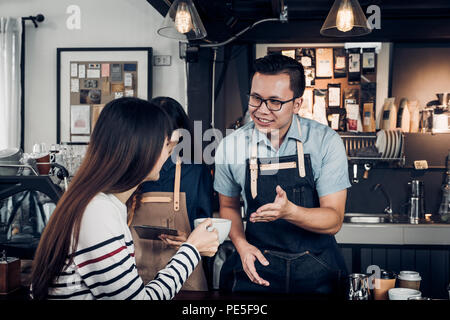 Male barista talking with customer about tasted of coffee cup with happy emotion at counter bar at cafe.coffee shop business owner concept,Service min - Stock Photo