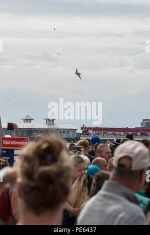 Blackpool, UK. 12 August 2018 - Crowds gather to watch the Blackpool airshow, including a performance by the RAF Red Arrows. The Red Arrows flew to the backdrop of an emerging storm, and performed for a crowd of tens of thousand along Blackpool's promenade.  Credit: Benjamin Wareing/Alamy Live News - Stock Photo