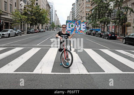 Washington D.C. USA.  12th August 2018. A woman stops her bike on a crosswalk on 14th street NW in Washington D.C. holding up a love sign as part of the counterprotest demonstrations against the 'Unite the Right 2' rally in nearby Lafayette Park.  As counterprotesters made their way up the street, instead of having barriers in place to have marchers turn left at the crossroad, this lone woman stood there supporting the counterprotesters as they made a turn directly in front of her. - Stock Photo